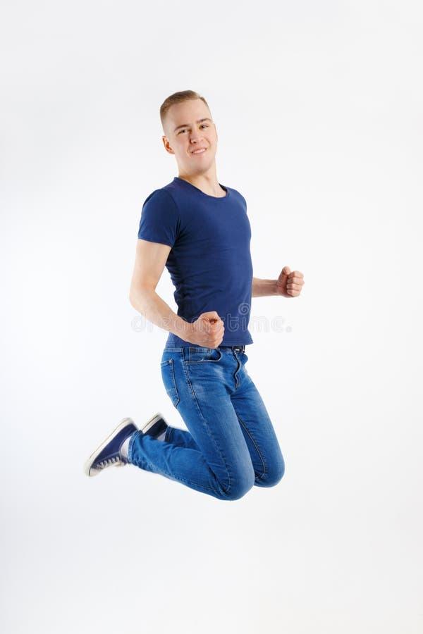 Le jeune homme bel heureux dans la chemise et des jeans bleus saute photographie stock