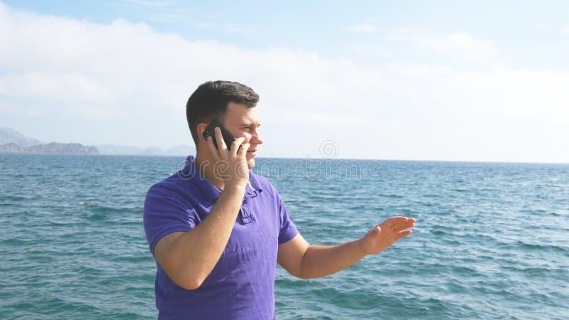 Le jeune homme bel parle au téléphone portable sur une plage de mer Type sérieux parlant du téléphone portable sur le fond de photo libre de droits