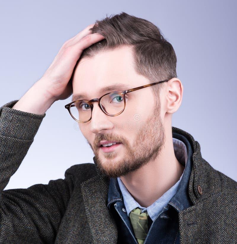 Le jeune homme bel redresse des cheveux, regardant l'appareil-photo élégant photographie stock libre de droits