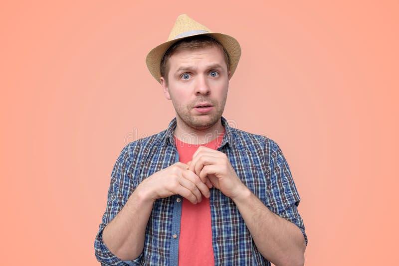 Le jeune homme bel timide dans le chapeau d'?t? est incertain images stock
