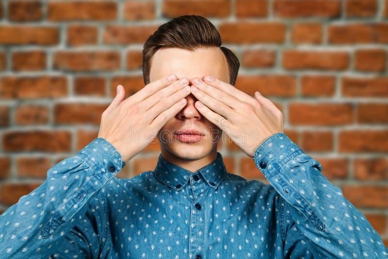 Le jeune homme blanc de portrait habillé dans la chemise bleue, ferme des yeux ses mains Portrait d'un homme sur un fond de mur d photographie stock libre de droits
