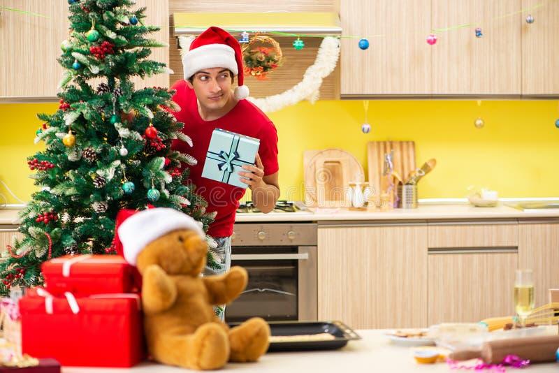 Le jeune homme célébrant Noël dans la cuisine photos libres de droits