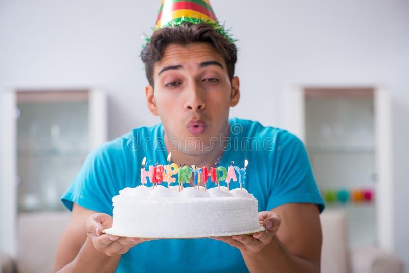 Le jeune homme célébrant seul l'anniversaire à la maison photo stock