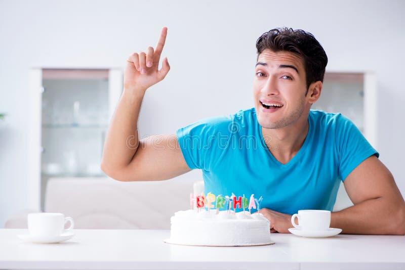 Le jeune homme célébrant seul l'anniversaire à la maison image libre de droits