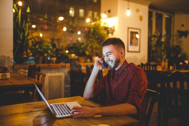 Le jeune homme caucasien bel avec la barbe et le sourire toothy dans la chemise rouge travaille derrière l'ordinateur portable, m photo stock