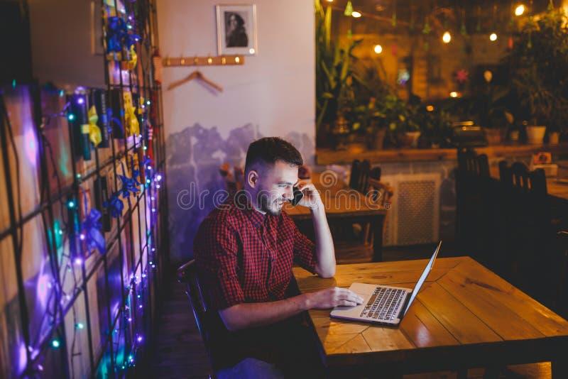 Le jeune homme caucasien bel avec la barbe et le sourire toothy dans la chemise rouge travaille derrière l'ordinateur portable, m photos libres de droits