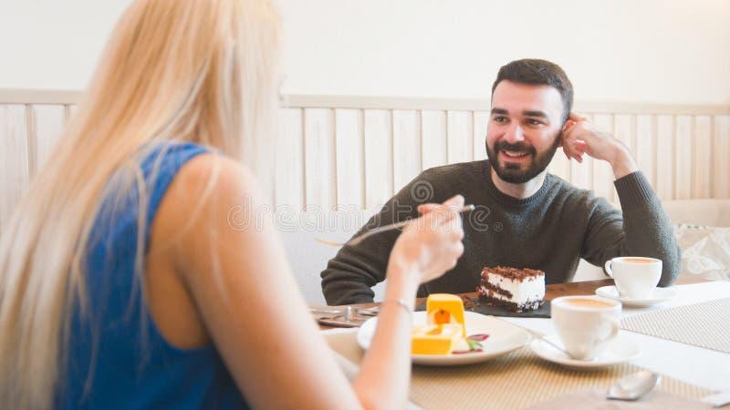 Le jeune homme caucasien devant la femme essaye des desserts dans le café photographie stock libre de droits
