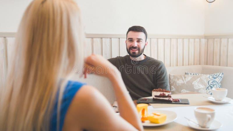 Le jeune homme caucasien devant la femme essaye des desserts dans le café photos stock