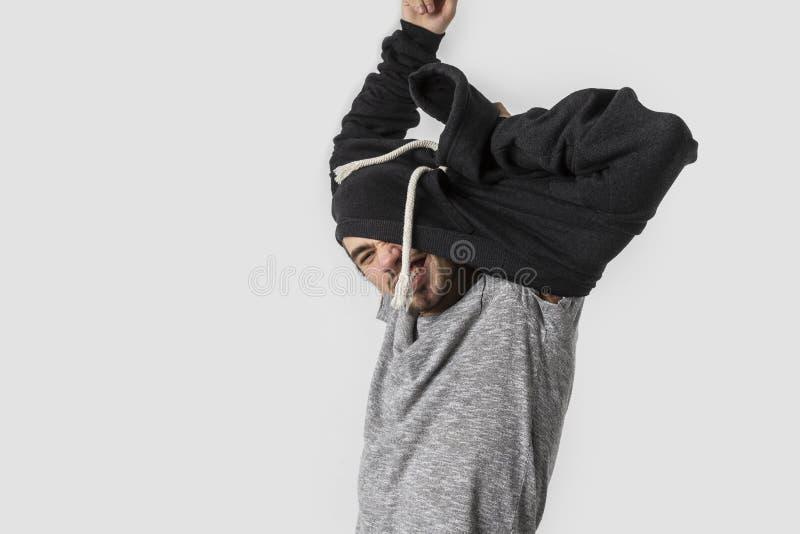 Le jeune homme caucasien très fatigué enlève heureusement ses vêtements après long et occupé jour D'isolement sur le fond blanc images stock