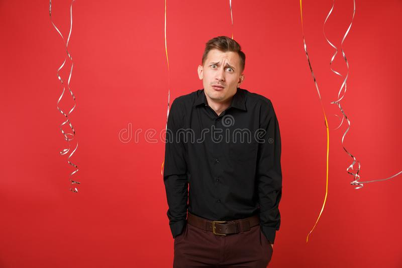 Le jeune homme concerné dans la chemise classique noire gesticule des épaules sur le fond rouge lumineux avec la serpentine ` S d image stock