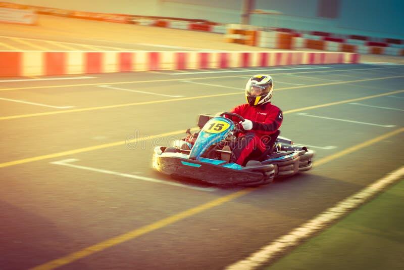 Le jeune homme conduit la voiture de kart avec la vitesse dans une voie d'emballage de terrain de jeu image stock