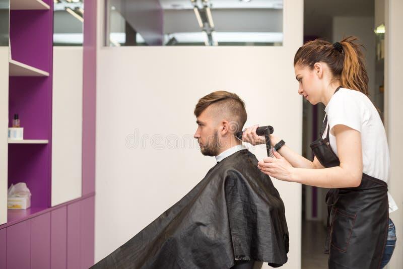 Le jeune homme coupe des cheveux dans le salon de coiffure photographie stock