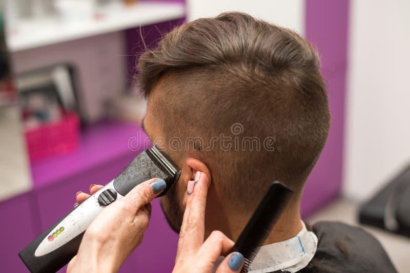 Le jeune homme coupe des cheveux dans le salon de coiffure photo stock