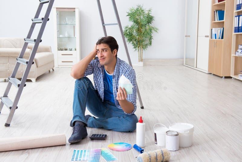 Le jeune homme dépensant trop son budget dans le projet de rénovation images libres de droits