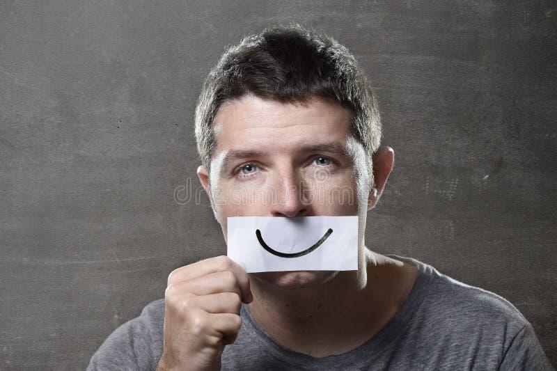 Le jeune homme déprimé a perdu dans la tristesse et la peine jugeant de papier avec le smiley sur sa bouche dans le concept de dé images libres de droits