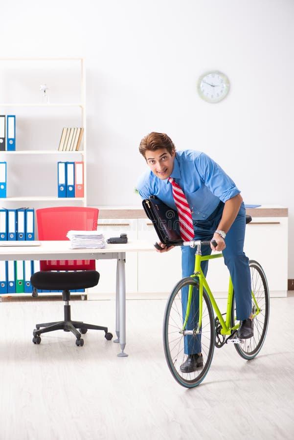 Le jeune homme d'affaires à l'aide du vélo pour permuter au bureau photo libre de droits