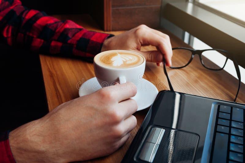 Le jeune homme d'affaires apprécie le café dans le café utilisant un ordinateur portable photo stock