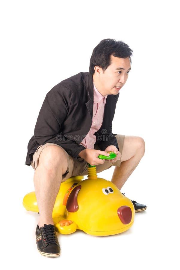 Le jeune homme d'affaires asiatique conduisant un ressembler de voiture de jouet de bébé au chien, est images stock
