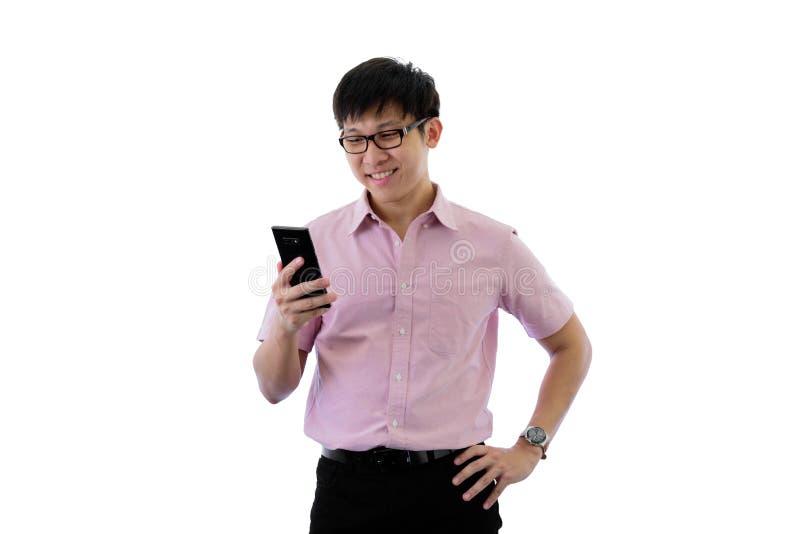 Le jeune homme d'affaires asiatique a debout et jouer le téléphone avec heureux sur d'isolement sur le fond de wihte photos stock