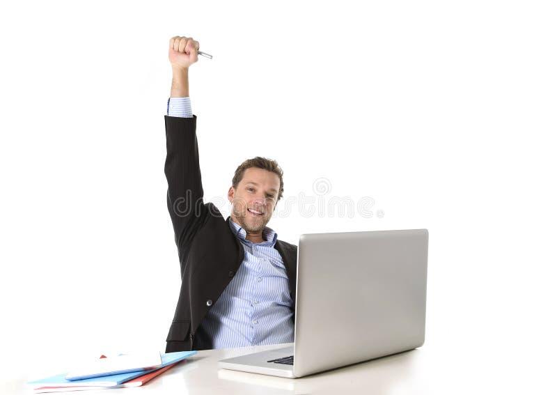 Le jeune homme d'affaires attirant heureux et agité au travail de bureau se reposant au bureau d'ordinateur a satisfait la célébr image stock