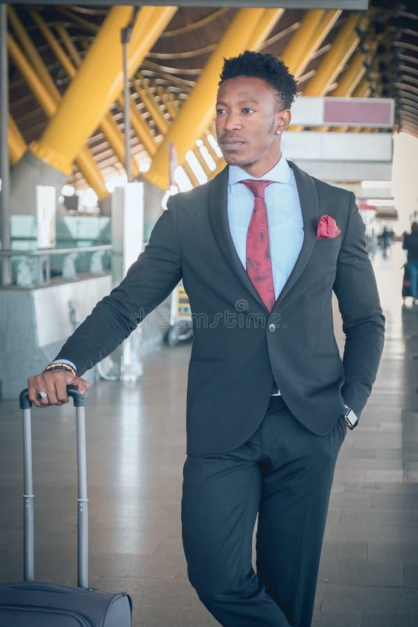 Le jeune homme d'affaires avec une valise se lève en dehors de l'airpo images libres de droits