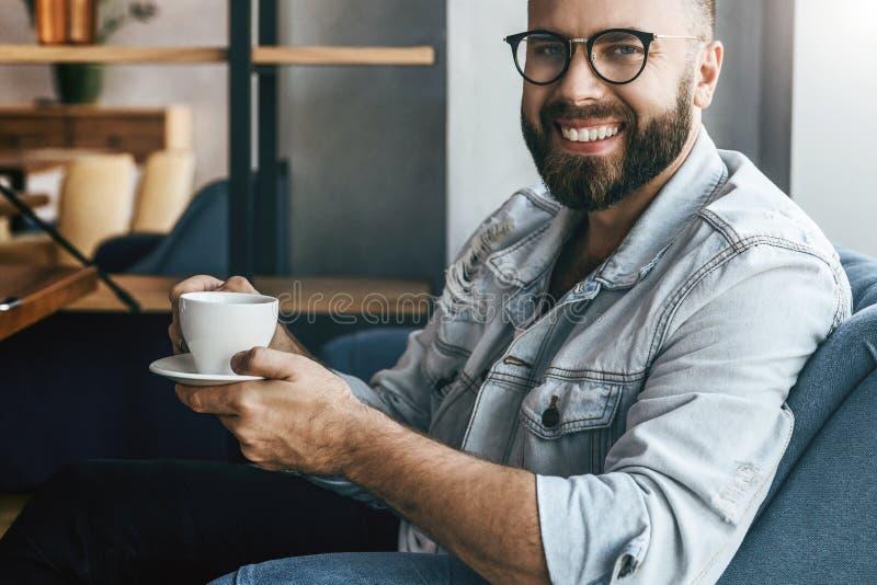 Le jeune homme d'affaires barbu attirant en verres à la mode s'assied en café, boit du café pendant le temps de déjeuner, repose, image stock