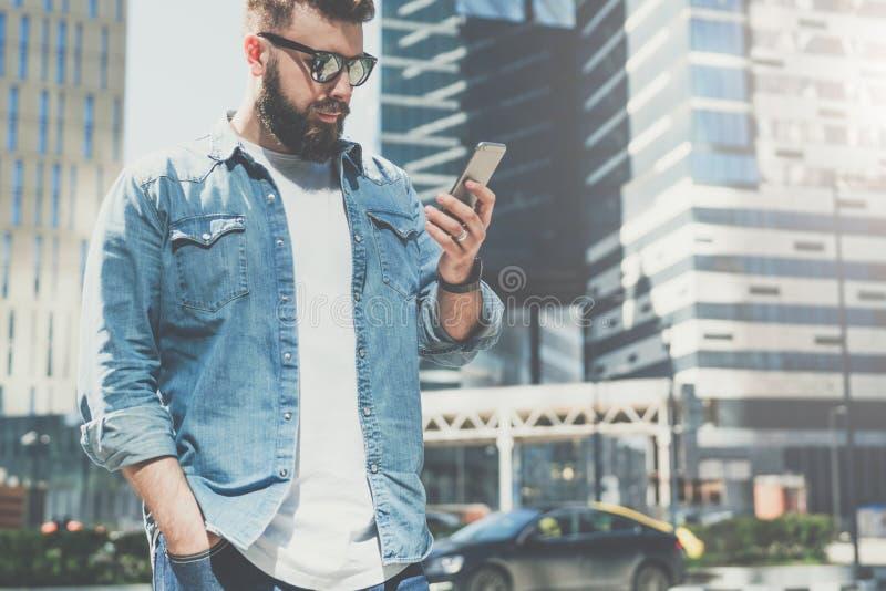Le jeune homme d'affaires barbu dans des lunettes de soleil se tient sur la rue de ville et utilise le smartphone L'homme lit l'i photographie stock libre de droits