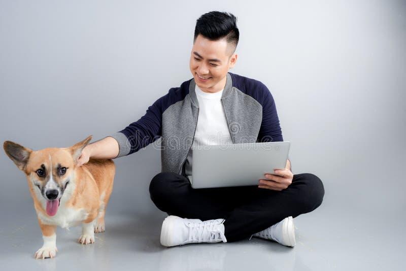 Le jeune homme d'affaires beau utilise l'ordinateur portable tout en se reposant avec son chien sur le plancher image stock