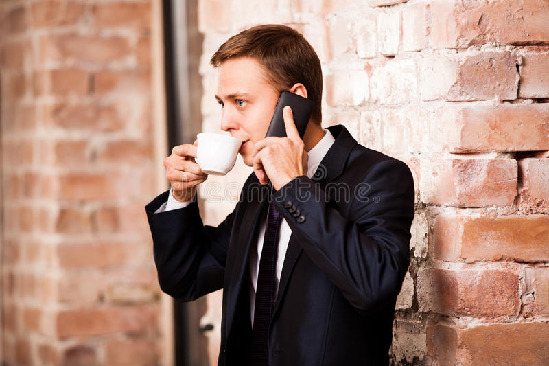 Le jeune homme d'affaires bel dans le costume noir boit du café et appelle par le téléphone près du mur de briques image stock