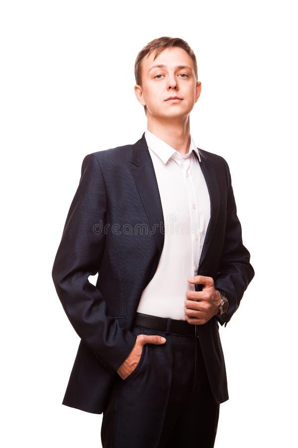Le jeune homme d'affaires bel dans le costume noir se tient droit et met ses mains dans des poches, portrait d'isolement dessus photos stock