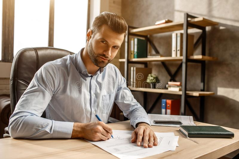 Le jeune homme d'affaires bel s'asseyent à l'écriture d'annonce de table dans son propre bureau Il a mis la signature sur des dou photos stock