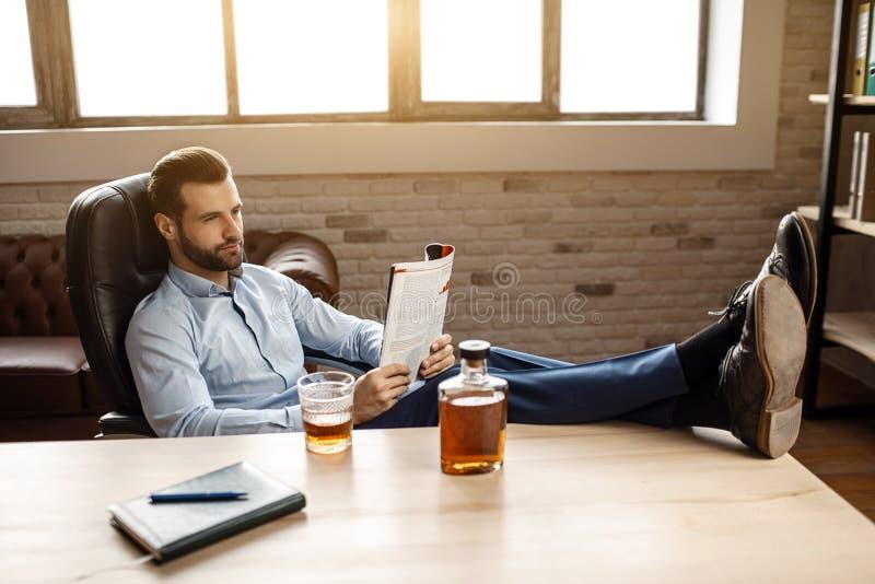 Le jeune homme d'affaires bel s'asseyent à la table et au journal lu dans son propre bureau Il tiennent des jambes sur le bureau  photo libre de droits