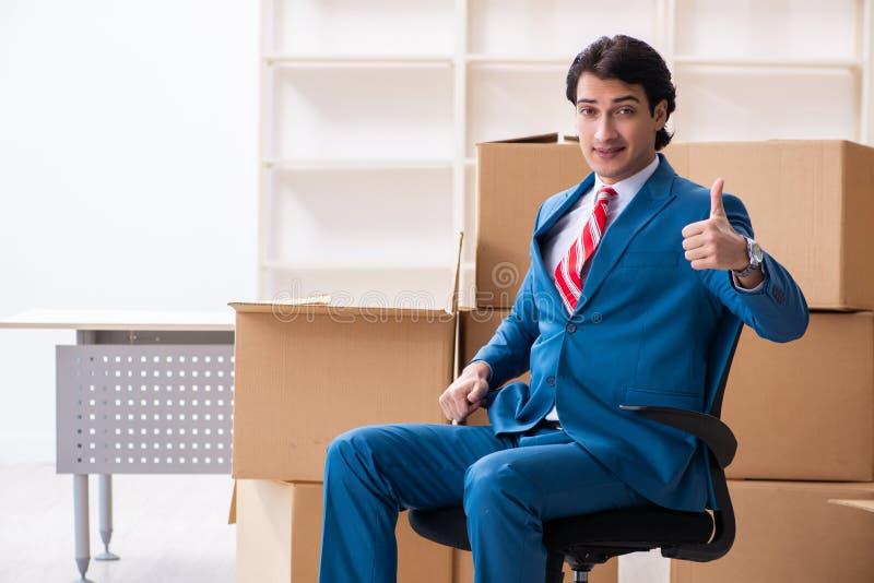 Le jeune homme d'affaires bel se déplaçant au nouveau lieu de travail photographie stock libre de droits