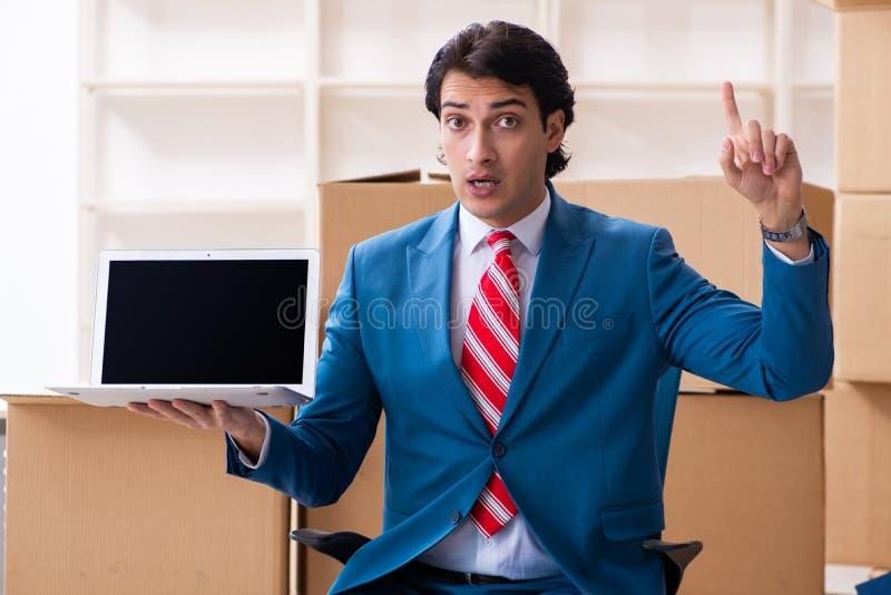 Le jeune homme d'affaires bel se d?pla?ant au nouveau lieu de travail photo stock