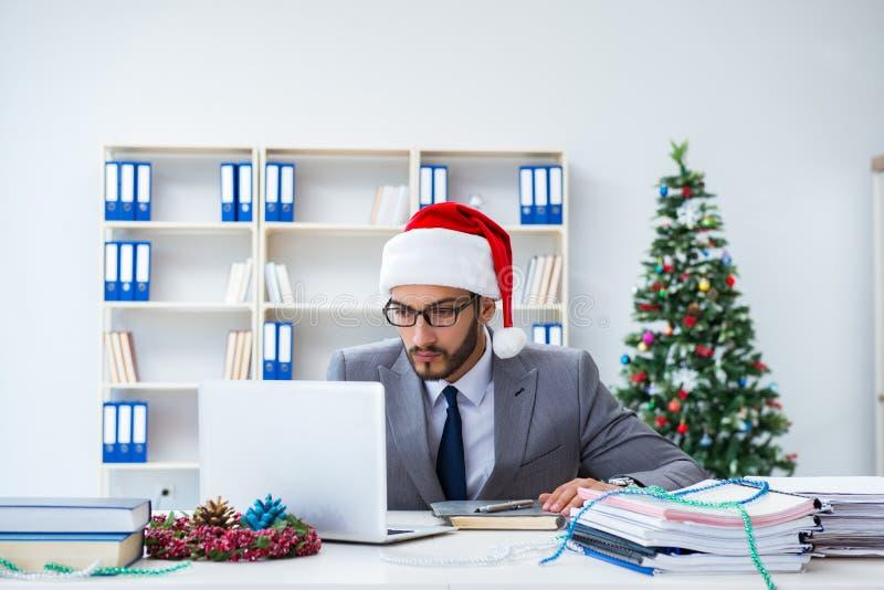 Le jeune homme d'affaires célébrant Noël dans le bureau images stock