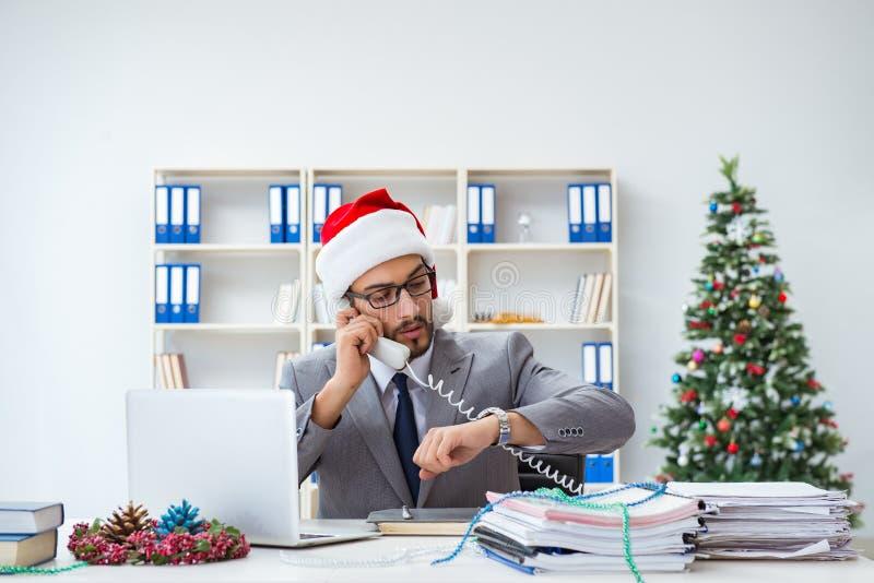Le jeune homme d'affaires célébrant Noël dans le bureau photo libre de droits