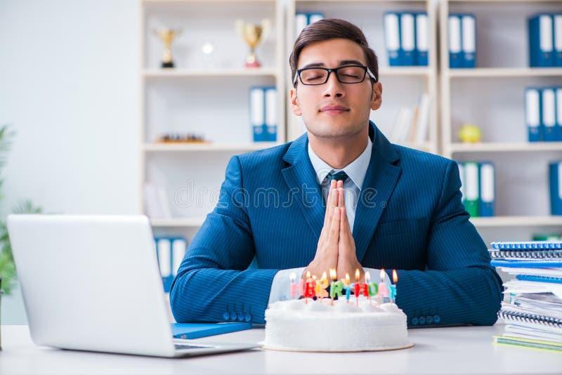 Le jeune homme d'affaires célébrant seul l'anniversaire dans le bureau photo libre de droits