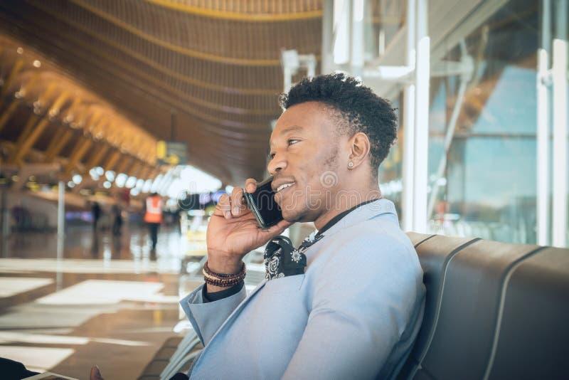 Le jeune homme d'affaires est assis dans l'aéroport souriant et parlant b image libre de droits