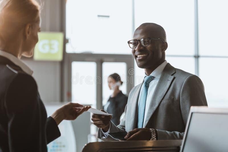 le jeune homme d'affaires heureux donnant le passeport et le billet au personnel à l'aéroport vérifient photographie stock libre de droits