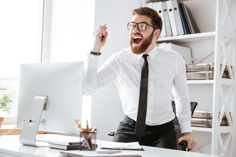 Le jeune homme d'affaires heureux font le geste de gagnant images stock