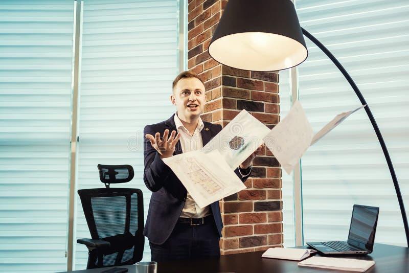 Le jeune homme d'affaires jetant un certain papier couvre dans le ciel, affaires image stock