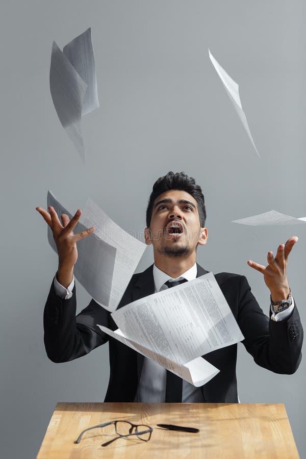 Le jeune homme d'affaires jetant un certain papier couvre sur le fond gris image stock