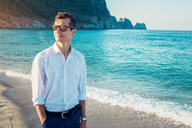 Le jeune homme d'affaires marche sur la plage photo stock