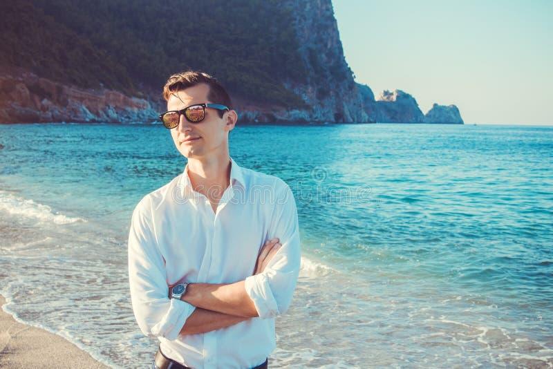 Le jeune homme d'affaires marche sur la plage photographie stock