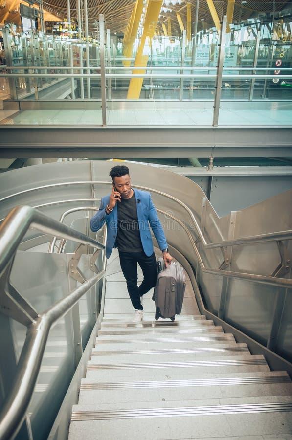 Le jeune homme d'affaires monte des escaliers dans l'aéroport parlant par t photo libre de droits