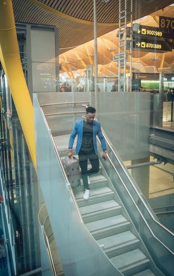 Le jeune homme d'affaires monte des escaliers dans l'aéroport parlant par t image libre de droits