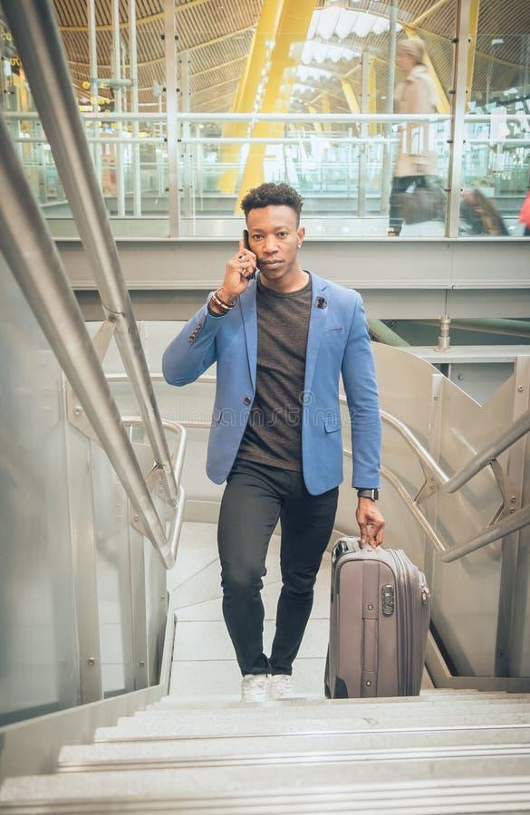 Le jeune homme d'affaires monte des escaliers dans l'aéroport parlant par t photos libres de droits