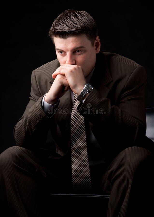 Le jeune homme d'affaires pensent sur le divan image stock