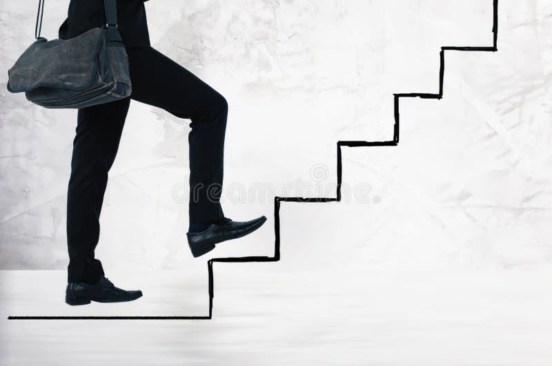 Le jeune homme d'affaires portent le sac de bride, marchant vers le haut des escaliers photo libre de droits