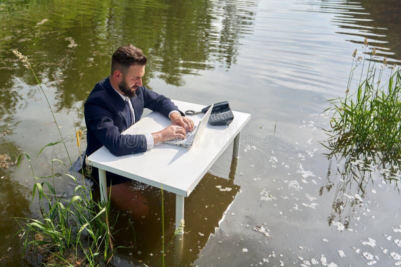 Le jeune homme d'affaires repose taille-profond dans un marais à un bureau photo libre de droits